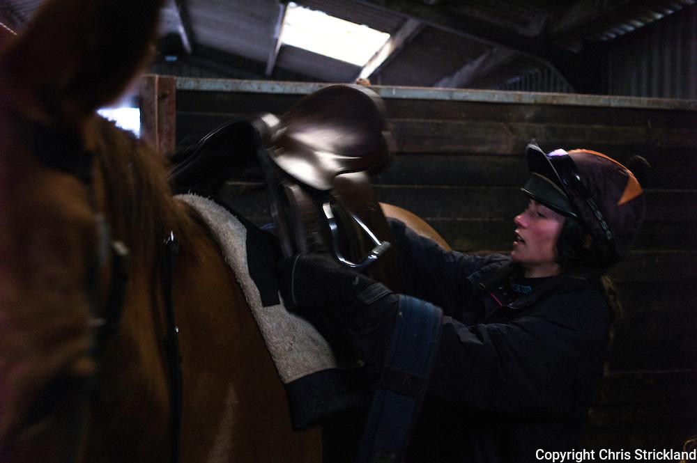 Jockey Joanna Walton tacks up Ginny ready for exercise the week before the Knight Frank Hunt Ride.