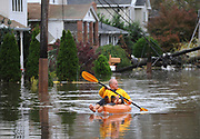 Boro Sangulin paddles a kayak through a flooded 16th Street from the effects of Hurricane Sandy on Tuesday; Oct.; 30; 2012; in Bayville; N.Y. Sangulin was checking on the flood damage of his home at the end of the block.  (AP Photo/Kathy Kmonicek)