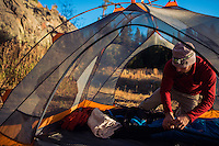Man setting up tent in Wyoming for a backpacking and camping trip.