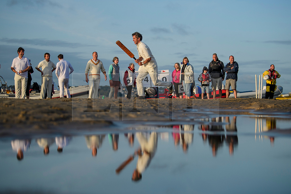 © Licensed to London News Pictures. 24/08/2017. Solent, UK. Teams take part in the Brambles Bank Cricket Match in the middle of The Solent strait on August 24, 2017. The annual cricket match between the Royal Southern Yacht Club and The Island Sailing Club, takes place on a sandbank which appears for 30 minutes at lowest tide. The game lasts until the tide returns. Photo credit: Ben Cawthra/LNP