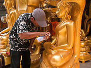 "05 JULY 2011 - BANGKOK, THAILAND:     A man uses gold spray paint to touch up a Buddha statue for sale on Bamrung Muang Street in Bangkok. Thanon Bamrung Muang (Thanon is Thai for Road or Street) is Bangkok's ""Street of Many Buddhas."" Like many ancient cities, Bangkok was once a city of artisan's neighborhoods and Bamrung Muang Road, near Bangkok's present day city hall, was once the street where all the country's Buddha statues were made. Now they made in factories on the edge of Bangkok, but Bamrung Muang Road is still where the statues are sold. Once an elephant trail, it was one of the first streets paved in Bangkok, it is the largest center of Buddhist supplies in Thailand. Not just statues but also monk's robes, candles, alms bowls, and pre-configured alms baskets are for sale along both sides of the street.       PHOTO BY JACK KURTZ"