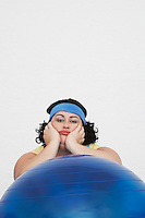 Uninspired overweight Woman Resting on Exercise Ball portrait