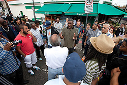 © Licensed to London News Pictures . FILE PICTURE DATED 07/08/2011 . Tottenham, UK . The morning after riots in Tottenham , people gather outside a food shop on Tottenham High Road and passionately argue about the causes and solutions . Photo credit : Joel Goodman/LNP