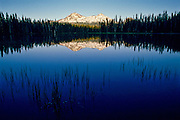Three Sisters mountains reflected in Scott Lake at sunset, Lane County, Oregon