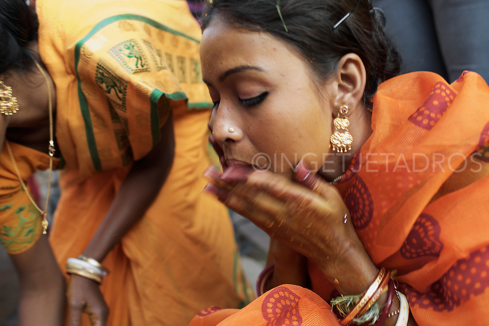 Mera is washing her face with Turmeric, the powder is mixed with water to form a paste and family members apply it to her face and body. It signifies the ritual purification and serves as a blessing of fortune and prosperity. Varanasi, India.