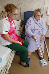 Occupational Therapist working with patient practicing how to use the helping hand aid prior to discharge,
