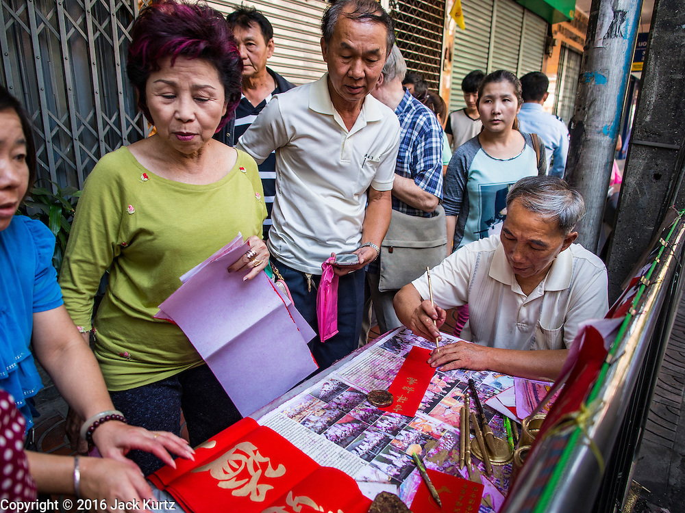 "04 FEBRUARY 2016 - BANGKOK, THAILAND:  People watch a traditional Chinese calligrapher write out New Years greetings in Bangkok's Chinatown district, before the celebration of the Lunar New Year. Chinese New Year, also called Lunar New Year or Tet (in Vietnamese communities) starts Monday February 8. The coming year will be the ""Year of the Monkey."" Thailand has the largest overseas Chinese population in the world; about 14 percent of Thais are of Chinese ancestry and some Chinese holidays, especially Chinese New Year, are widely celebrated in Thailand.     PHOTO BY JACK KURTZ"