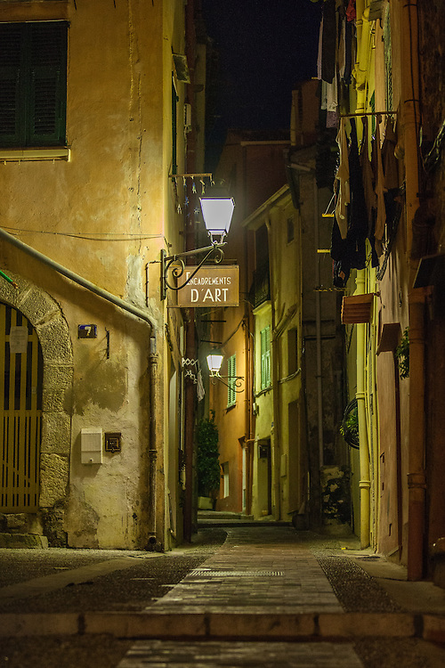 A narrow street in Menton's Old Town. It's night and the lamps show off the beautiful soft colours of this Riviera town.