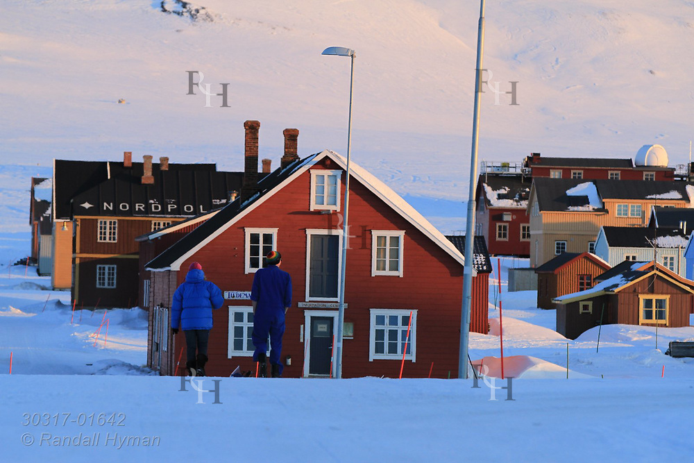 Two people walk through snow on a late April evening at the international science village of Ny-Alesund on Spitsbergen island in Kongsfjorden; Svalbard, Norway.
