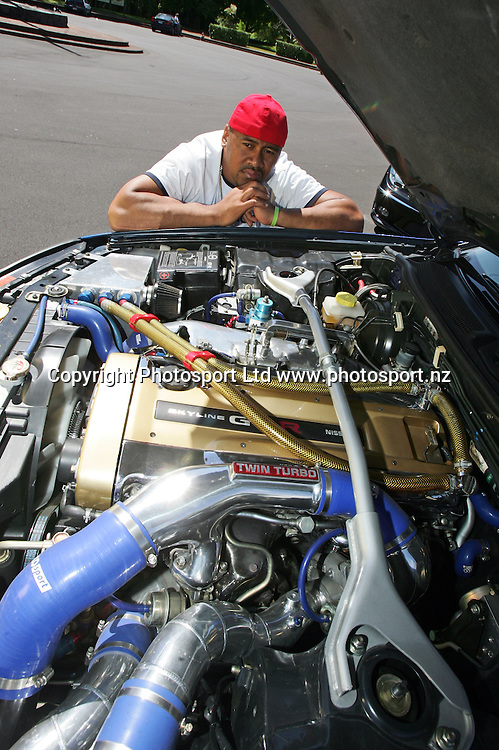 Jonah next to the engine bay of one of his cars. Photoshoot of Jonah Lomu and his cars at Cornwall Park, Auckland. 31 October 2005. Copyright photo: Andrew Cornaga / www.photosport.nz