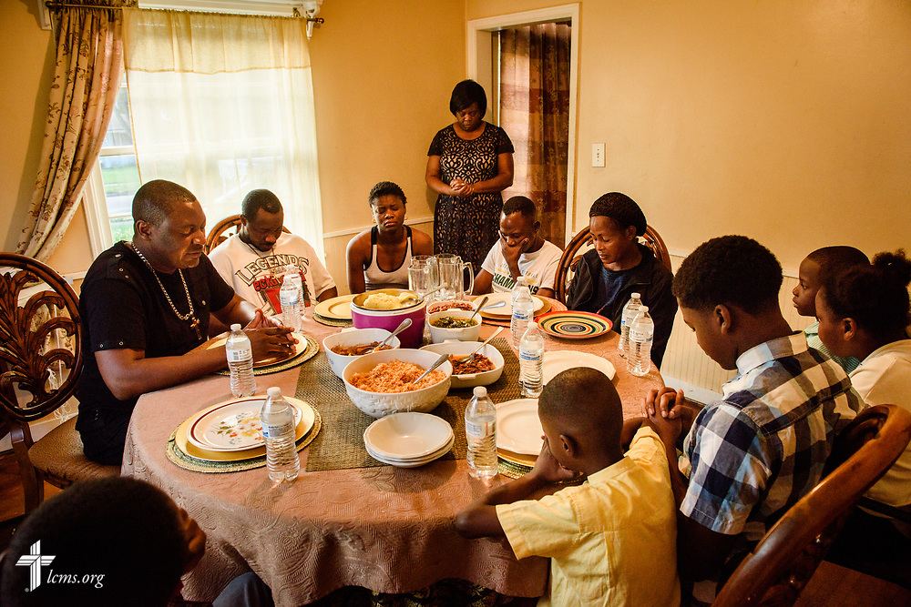 The Rev. Gui Kasongo Kabeo (left), pastor at Eglise Lutherienne Internationale de Sion (International Lutheran Church of Zion) and Gospel Lutheran Church, both in Milwaukee, Wis., prays before dinner at his home on Monday, Aug. 14, 2017 in Milwaukee. Kabeo houses refugees, some seen in this photograph, who do not have a place to go when they arrive in the United States. LCMS Communications/Erik M. Lunsford