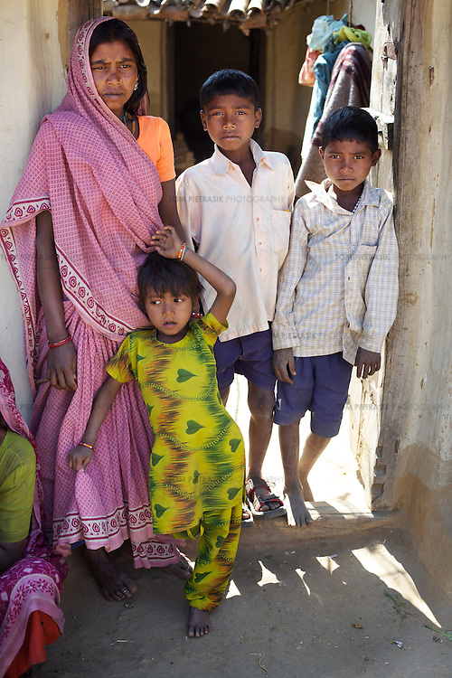 Hiralal's widow Meena Devi, 28, with their daughter Sarita, 7, and sons Aditya, 11, and Sanjeet, 9...Hiralal died, aged 30, along with 13 others from Jalhe Bogiya village in May 2005 when, compelled by hunger, he ate the rotten meat of a goat that had died two days previously. Hiralal was a day wage farm labourer but drought conditions meant that there was little work and he had not been able to find employment for the year prior to his death. He and his family regularly experienced hunger surviving on just fruit and berries. His widow Meena Devi, 28, must now provide for their three children. She lives with Hira's mother Bhikni Devi, 50, and father Nanku Bhuiyan, 55. Meena earns a living by  collecting firewood, a two day task for which she earns Rs.30. The family receives subsidized grain and kerosine for twelve days a month as part of the PDS (Public Distribution System) and the children benefit from the recently introduced daily meals provided by the local school and Anganwadi (child-care) centre. They have three cows that they do not own but rear and feed for which they are supplied milk for their own consumption. When each of the cows are sold, the Meena and her family will receive half the value raised, the rest going to the owner who is from the Yadav caste. ..Lack of irrigation and food security lie at the root of the Maha Dalit community's problems in the village of Jalhe Bogiya. In the exploitative and divisive caste system, Maha Dalits are considered the lowest of the low. Ostracized by wider society (including the administration) illiteracy runs as high as 95 percent. Jalhe Bogiya now has an - as yet incomplete - access-road built as part of the NREGA (National Rural Employment Guarantee Scheme). Intervention by NGOs in summer 2010 successfully lobbied the local administration to implement the provision of school midday meals which, by law is the right of every child. It is alleged that the Anganwadi (pre-school) centre administrator, syphons off food m