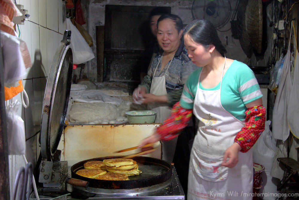 Asia, China, Chongqing. Local street market in the city of Chongqing - woman cooking a local specialty pancake bread.
