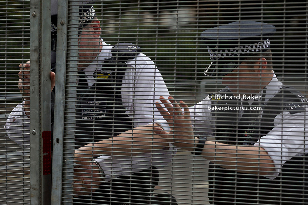 UK Met police officers guard a temporary perimeter fence encircling Winfield House, the official residence of the US Ambassador during the visit to the UK of US President, Donald Trump, on 12th July 2018, in Regent's Park, London, England.