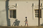 Southern Africa. Mozambique. Ilha de Mocambique. Stone town. Youth with football passing Portuguese architecture..DVD0013