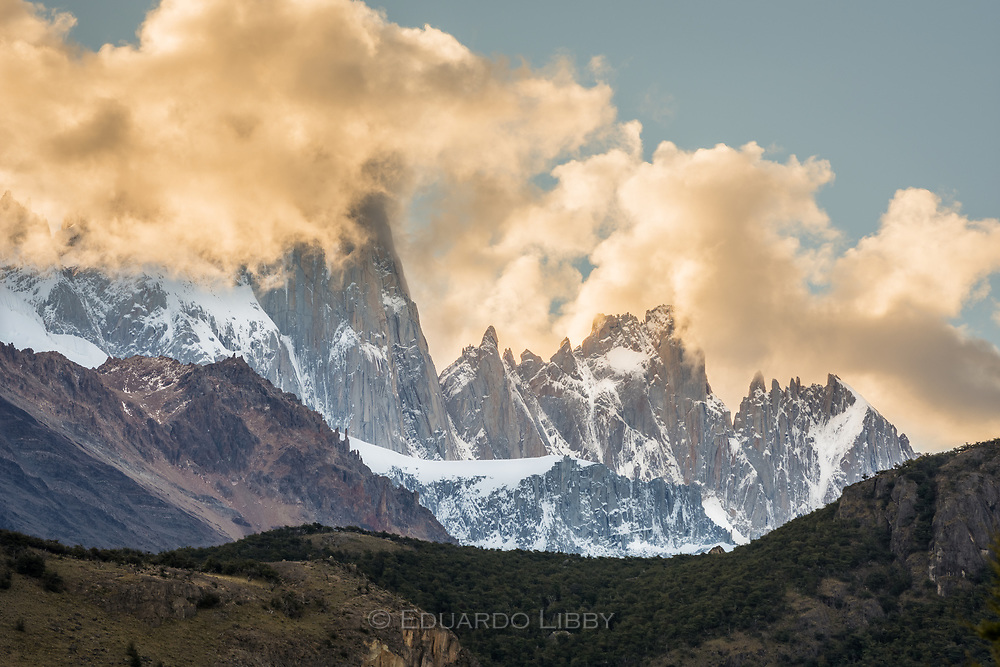 The afternoon sun lights the clouds shrouding Mount Fitzroy Range. View from El Chalten.