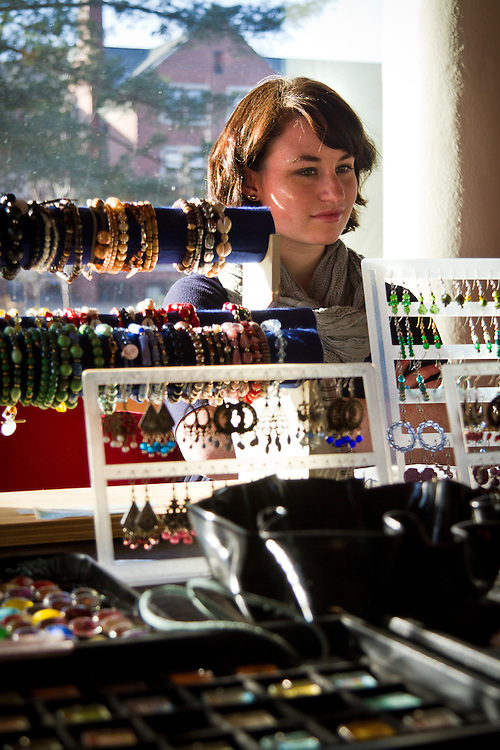 Grinnell art fair regular Jill McFee sits for a moment of repose behind rows of her handmade jewelry at last Sunday's art and craft fair in JRC 101.