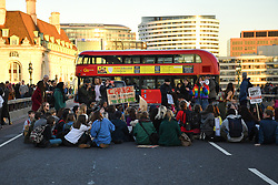 © Licensed to London News Pictures 15/02/2019 London, UK. A routemaster bus is forced to make a u-turn on Westminster Bridge as schoolchildren stage a sit-down. At the close of a day of protest, students who took the day off school to protest inaction over climate change move from Parliament Square to Westminster Bridge blocking traffic at rush hour. Photo credit: Guilhem Baker/LNP