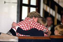 The Princess of Wales hugs her eldest son Prince William, aged 10, after boarding the Royal Yacht Britannia with her husband, the Prince of Wales and her younger son, Prince Harry.