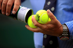 A line judge removes new balls from a canister on day one of the Wimbledon Championships at the All England Lawn Tennis and Croquet Club, Wimbledon.