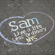 Chalk Street Art quote &quot; Sam Live a Life Less Ordinary  NYC &quot; on<br /> the side walk in Washington Square Park.<br /> <br /> Street art can be a powerful platform for reaching people in public spaces.