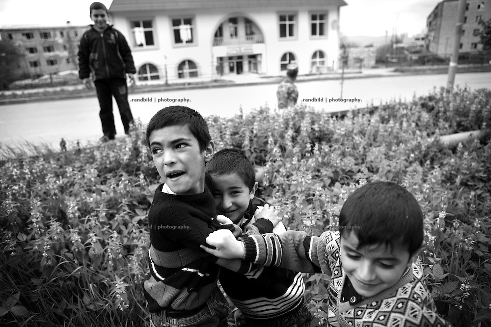 "Boys contest their physical power in the streets of Shushi. This image is part of the photoproject ""The Twentieth Spring"", a portrait of caucasian town Shushi 20 years after its so called ""Liberation"" by armenian fighters. In its more than two centuries old history Shushi was ruled by different powers like armeniens, persians, russian or aseris. In 1991 a fierce battle for Karabakhs independence from Azerbaijan began. During the breakdown of Sowjet Union armenians didn´t want to stay within the Republic of Azerbaijan anymore. 1992 armenians manage to takeover ""ancient armenian Shushi"" and pushed out remained aseris forces which had operate a rocket base there. Since then Shushi became an ""armenian town"" again. Today, 20 yeras after statement of Karabakhs independence Shushi tries to find it´s opportunities for it´s future. The less populated town is still affected by devastation and ruins by it´s violent history. Life is mostly a daily struggle for the inhabitants to get expenses covered, caused by a lack of jobs and almost no perspective for a sustainable economic development. Shushi depends on donations by diaspora armenians. On the other hand those donations have made it possible to rebuild a cultural centre, recover new asphalt roads and other infrastructure. 20 years after Shushis fall into armenian hands Babies get born and people won´t never be under aseris rule again. The bloody early 1990´s civil war has moved into the trenches of the frontline 20 kilometer away from Shushi where it stuck since 1994. The karabakh conflict is still not solved and could turn to an open war every day. Nonetheless life goes on on the south caucasian rocky tip above mountainious region of Karabakh where Shushi enthrones ever since centuries."