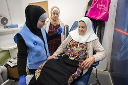 26 February 2020, Abu Dis, Palestine: 87-year-old Diabetes patient Hamama Jaffal from Abu Dis prepares for a foot exam as she visits the Augusta Victoria Hospital's Mobile Diabetes Clinic. Here, sitting down with the support of nurse Najwa Hawamdeh (left) and Nurse Baraa Radayda (centre) who joins the team from the Ministry of Health clinic of the Palestinian Authority in Abu Dis to learn from the staff of the Augusta Victoria Hospital's mobile diabetes clinic. In an effort to make Diabetes services more accessible to people in the West Bank, the Augusta Victoria Hospital offers a Mobile Diabetes Clinic, which moves around to various locations in the West Bank, offering screening and routine testing for Diabietes and the symptoms it causes.