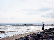 A man standing on a pile of stones placed to break the waves on the artificial beach in Serangan. In 1996, the island was reclaimed and widened from 112 hectares to 365 hectares but the project would later be halted due to the monetary crisis hitting Indonesia in 1998. The reclamation caused damage to its ecosystem. According to a record, around 3,5 million tourists from around the world visited the island for vacation in 2014. Most of them preferred staying in the southern coast such as in Kuta, Nusa Dua, and Sanur. These are the tourism hubs of Bali that naturally attract investors' interest to build hotels and other leisure establishments. The island's tourism is indeed inseparable from its southern coast's history, an area blessed with breathtaking beaches. It is from here the Bali holiday business began to develop as the influx of Australian hippies and surfers to Kuta started back in the 70s. The fishermen's villages would later transform drastically because of it. Hotels, restaurants, and other facilities were growing and spreading along the coast so fast like mushrooms in a rainy season.
