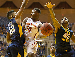 Feb 22, 2016; Morgantown, WV, USA; Iowa State Cyclones guard Deonte Burton (30) passes under the basket while defended by West Virginia Mountaineers guard Tarik Phillip (12) during the first half at the WVU Coliseum. Mandatory Credit: Ben Queen-USA TODAY Sports