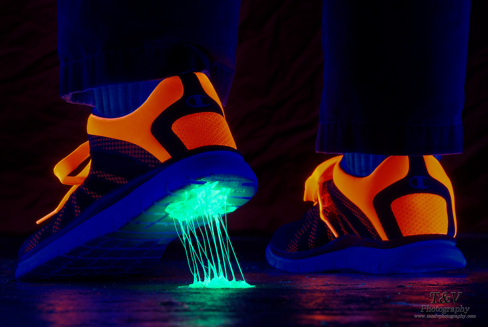 Glowing gum stuck on the bottom of a tennis shoe.Black light
