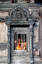 Children of the World Series:  Two young monks-in-training view the world through a temple window in Chiang Mai, Thailand.