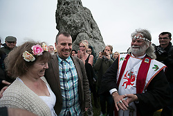 © Licensed to London News Pictures. 21/06/2015. Salisbury, UK  Picture shows Druid leader Arthur Pendragon marry a couple as the sun rises.  The Summer Solstice Festival takes place at Stonehenge.  The annual celebration of the longest day of the year, attracting tens of thousands of spectators, including Druids, tourists, locals and others. Photo credit : Laura Dale/LNP