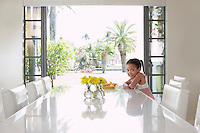 Girl (5-6 years) sitting at dining table