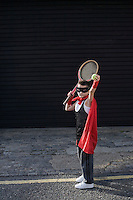 Boy wearing Zorro costume with tennis racket
