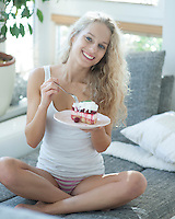 Full length portrait of woman having raspberry cake on sofa