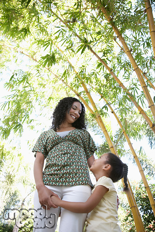 Girl (5-6 years) hugging mother standing in bamboo forest low angle view