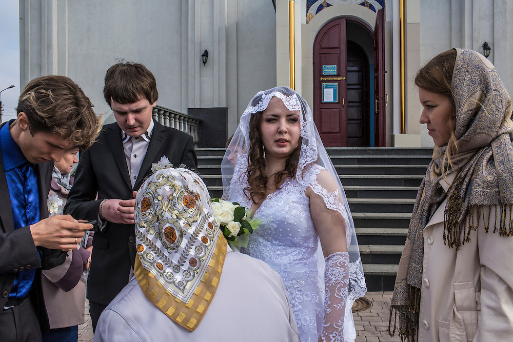 A bride and groom, along with friends and family, leave Saint Pokrovsky Church after their wedding on Friday, October 17, 2014 in Donetsk, Ukraine. Photo by Brendan Hoffman, Freelance