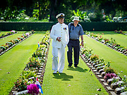"11 NOVEMBER 2018 - KANCHANABURI, KANCHANABURI, THAILAND:  J.P. VAN DER MEULEN, left, a veteran of the Dutch Navy, walks through Kanchanaburi War Cemetery before the Rememberance Day ceremony in Kanchanaburi, Thailand. Kanchanaburi is the location of the infamous ""Bridge On the River Kwai"" and was known for the ""Death Railway"" built by Japan during World War II using allied, principally British, Australian and Dutch, prisoners of war as slave labor. There are 6,982 people buried in the cemetery, including 5,000 Commonwealth soldiers and 1,800 Dutch soldiers. November 11, 2018 marked the 100th anniversary of the end of World War I, celebrated as Rememberance Day in the UK and the Commonwealth and Veterans' Day in the US..     PHOTO BY JACK KURTZ"