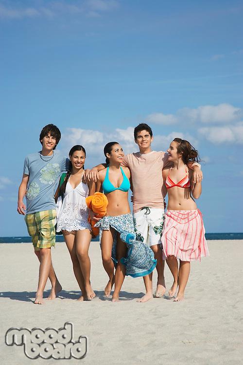 Group of teenagers (16-17) walking on beach portrait