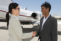 Two mid-adult businesswomen shaking hands in front of private plane on runway.