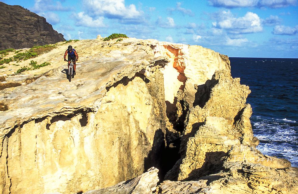 Mountain biker cycling along seaside cliff, Kauai, Hawaii