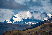 Distant glacier-clad Southern Alps seen southwest of Gillespie Pass in Mount Aspiring National Park, Otago region, South Island of New Zealand. UNESCO lists Mount Aspiring as part of Wahipounamu - South West New Zealand World Heritage Area.