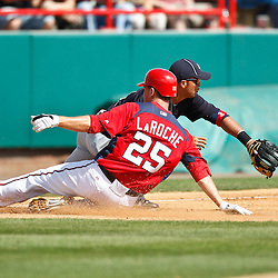 March 4, 2011; Viera, FL, USA; Washington Nationals first baseman Adam LaRoche (25) slides in safe past Atlanta Braves third baseman Martin Prado (14) during a spring training exhibition game at Space Coast Stadium. Mandatory Credit: Derick E. Hingle-US PRESSWIRE