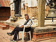 04 MARCH 2017 - KATHMANDU, NEPAL: An elderly Nepali man sits in the sun at a temple in the Social Welfare Centre, Elderly's Home, the only public nursing home in Nepal. The 2015 earthquake badly damaged the temple. Recovery seems to have barely begun nearly two years after the earthquake of 25 April 2015 that devastated Nepal. In some villages in the Kathmandu valley workers are working by hand to remove ruble and dig out destroyed buildings. About 9,000 people were killed and another 22,000 injured by the earthquake. The epicenter of the earthquake was east of the Gorka district.     PHOTO BY JACK KURTZ