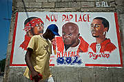 A pedestrian passes a mural memorializing the lives of three members of the well-known rap kreyol group Barikad Crew in downtown Port-au-Prince, Haiti on July 21, 2008. The rappers' deaths in a fiery automobile accident the month prior resulted in an outpouring of support for them and the remaining 8 members of Barikad Crew when between 60,000 and 100,000 individuals descended on the city for their funeral. The support highlighted the popularity of the largely underground rap kreyol movement and has inspired a number of young groups to try to fill their shoes.