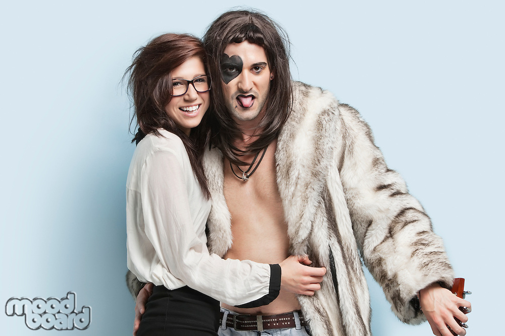 Young man in fur coat sticking out tongue while standing with happy woman against light blue background