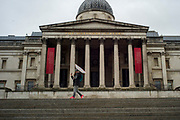 UNITED KINGDOM, London: 28 April 2020 <br /> A member of the public walks in front of The National Gallery in Trafalgar Square during a wet and miserable morning. The weather is set to stay wet for the next few days according to the Met Office.