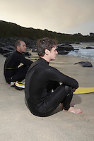 Two surfers sitting on beach looking at sea side view