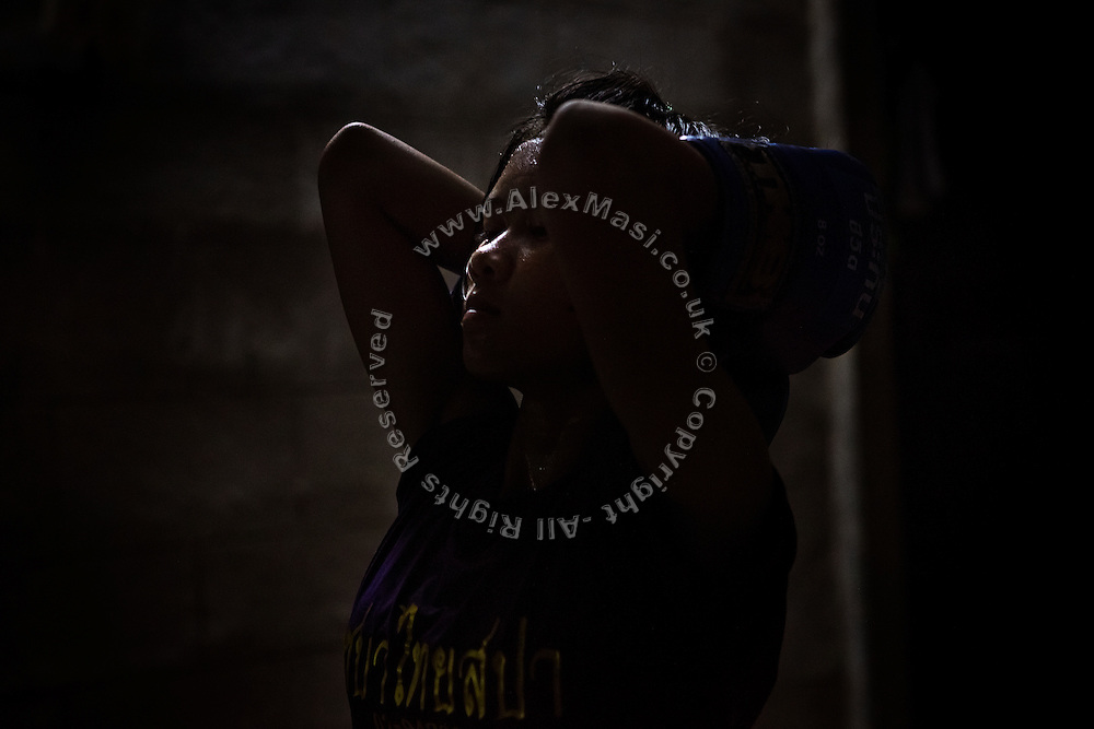 Phatsorn Bunmasen, 14, is breathing deeply after training hard until evening at the gym where she practises Muay Thai boxing, in a village near Ubon Ratchathani, northeast Thailand.