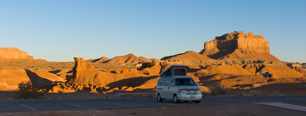 A Volkswagon Eurovan pop top Camper parks by a golden butte at sunrise. Admire fanciful hoodoos, mushroom shapes, and rock pinnacles in Goblin Valley State Park, in Emery County between the towns of Green River and Hanksville, in central Utah, USA. The Goblin rocks eroded from Entrada Sandstone, which is comprised of alternating layers of sandstone (cross-bedded by former tides), siltstone, and shale debris which were eroded from former highlands and redeposited in beds on a former tidal flat.